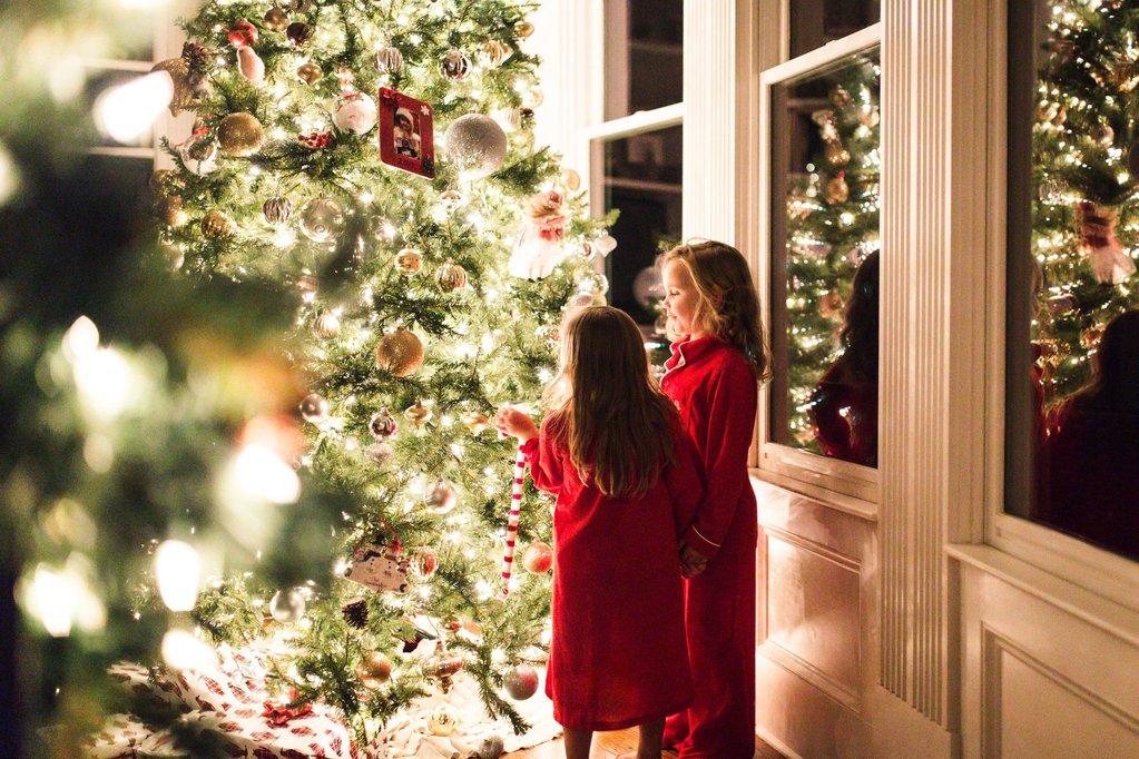 Foto de niños colgando adornos en el árbol de Navidad