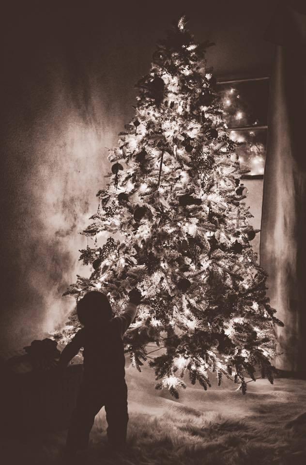 Fotografía en blanco y negro de un niño apuntando al árbol de Navidad