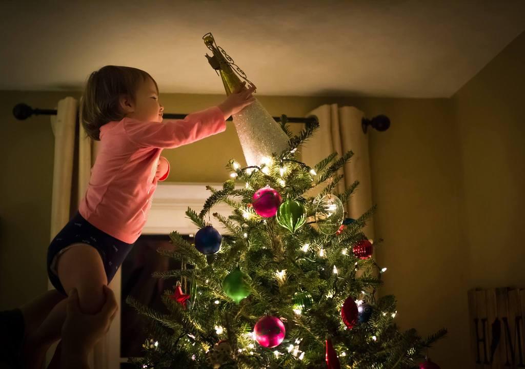 Foto de niña colocando un ángel encima del árbol de Navidad