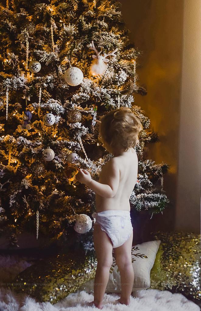 Imagen de niño en pañal decorando el árbol de Navidad