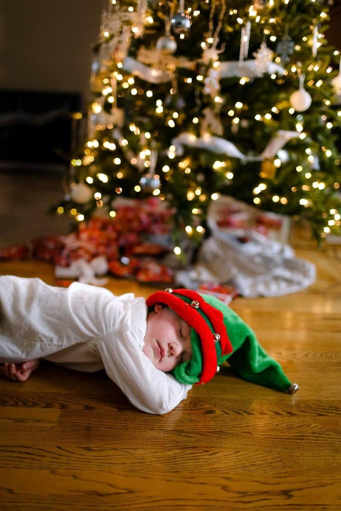 Foto de niño durmiendo delante del árbol de Navidad