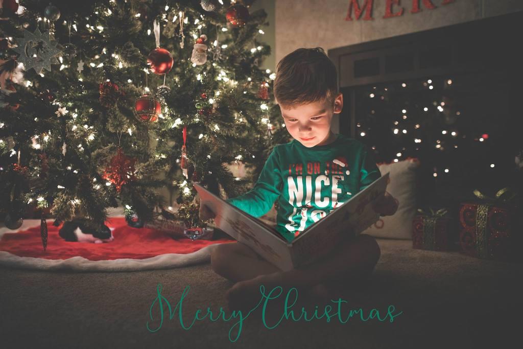 Niño leyendo un libro mágico delante del árbol de Navidad