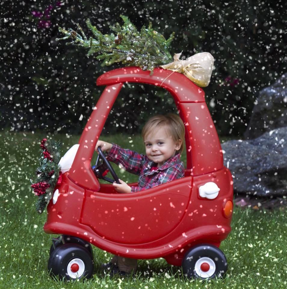 Niño conduciendo un coche de juguete con árbol de Navidad en la parte superior