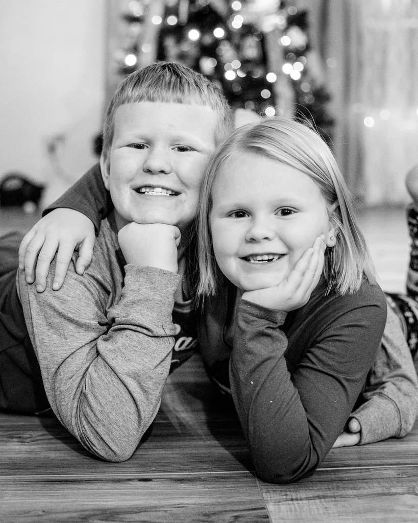 Foto retrato de niños sonriendo delante del árbol de Navidad