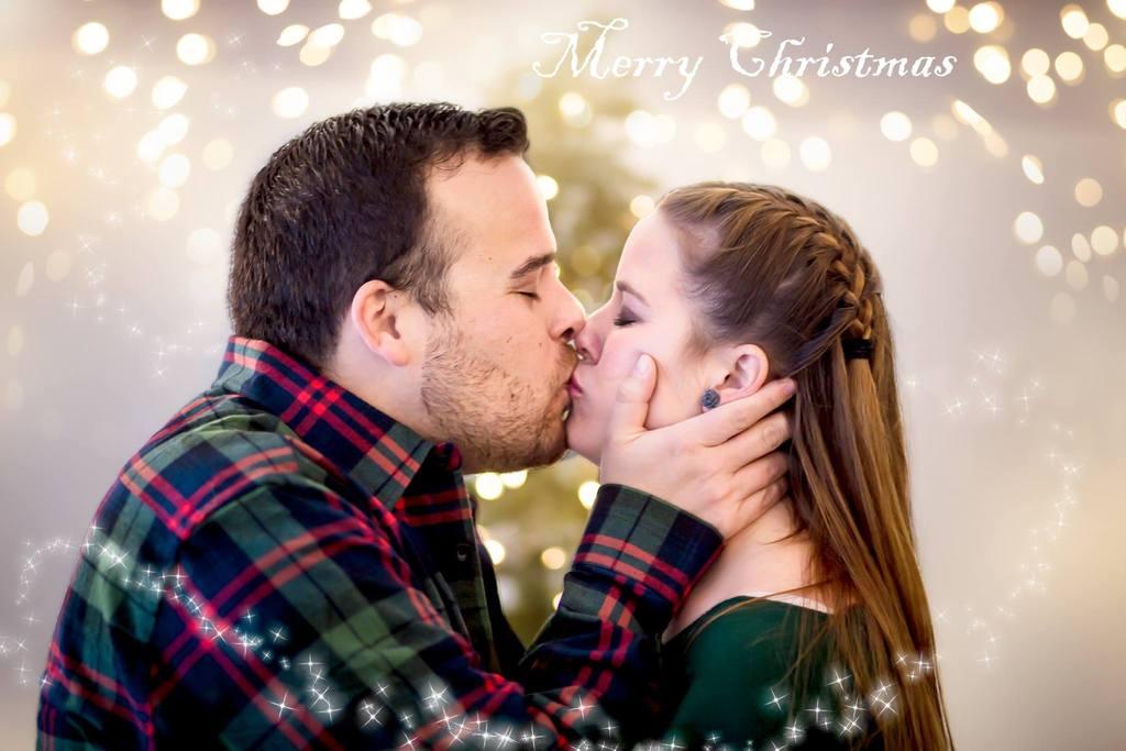 Imagen de pareja besándose delante del árbol de Navidad