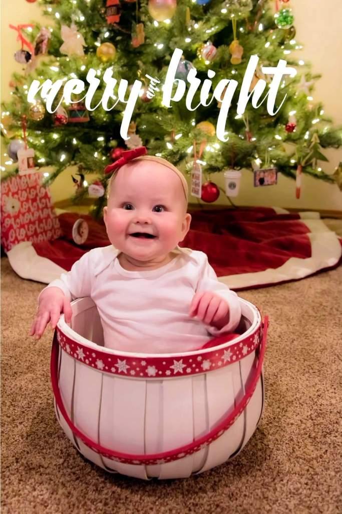 Bebé en la canasta delante del árbol de Navidad