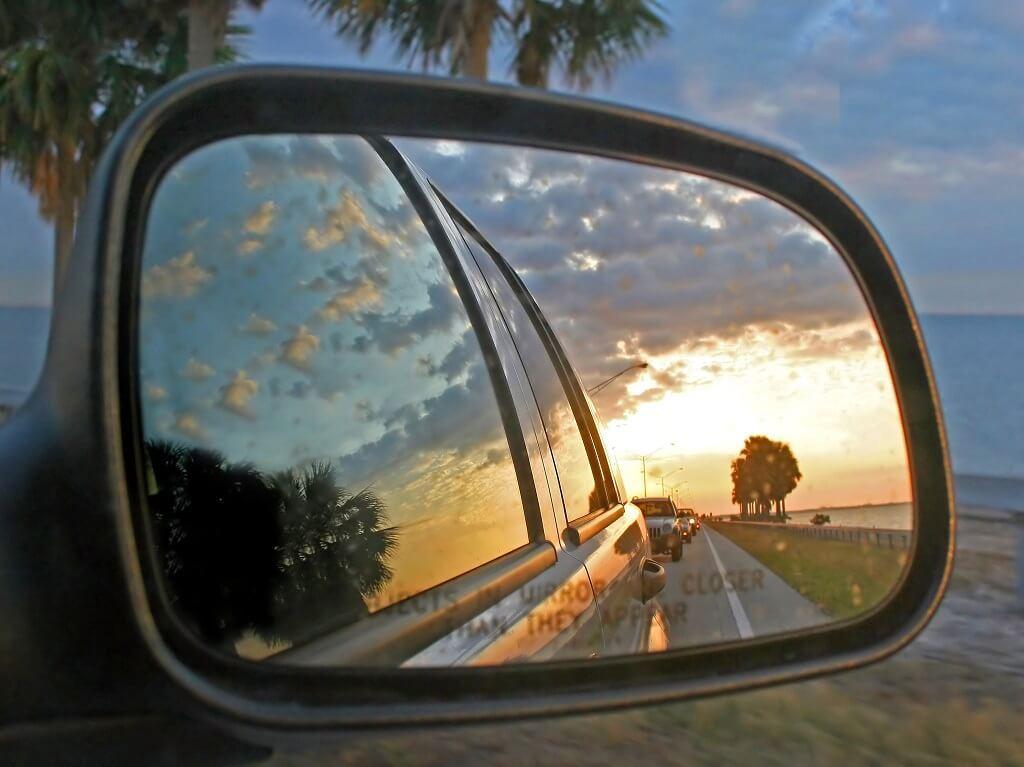 Foto en perspectiva de una puesta de sol desde la perspectiva de un espejo retrovisor