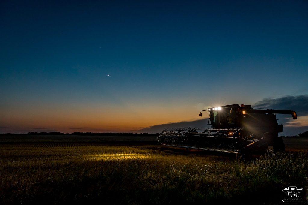 Foto nocturna de la cosechadora de la granja.