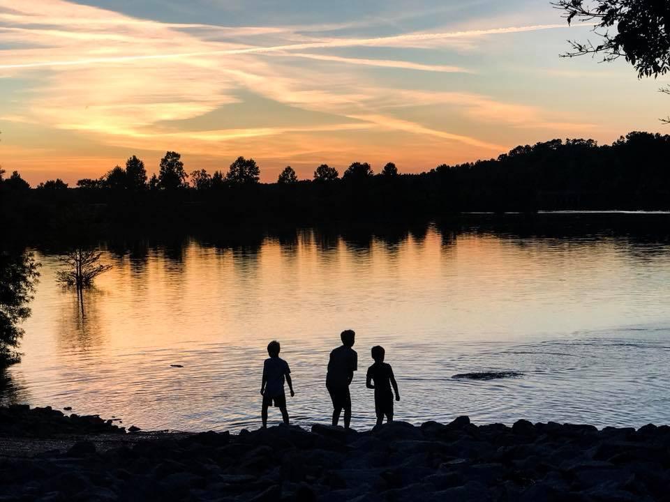 Silueta de foto nocturna de niños saltando rocas en el lago