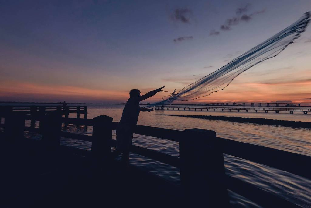 Foto nocturna del hombre lanzando una red de pesca