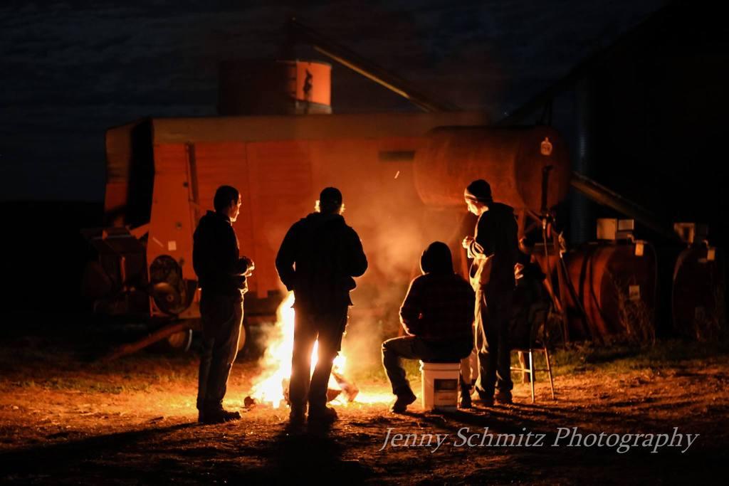 Foto nocturna de amigos parados alrededor de una fogata.