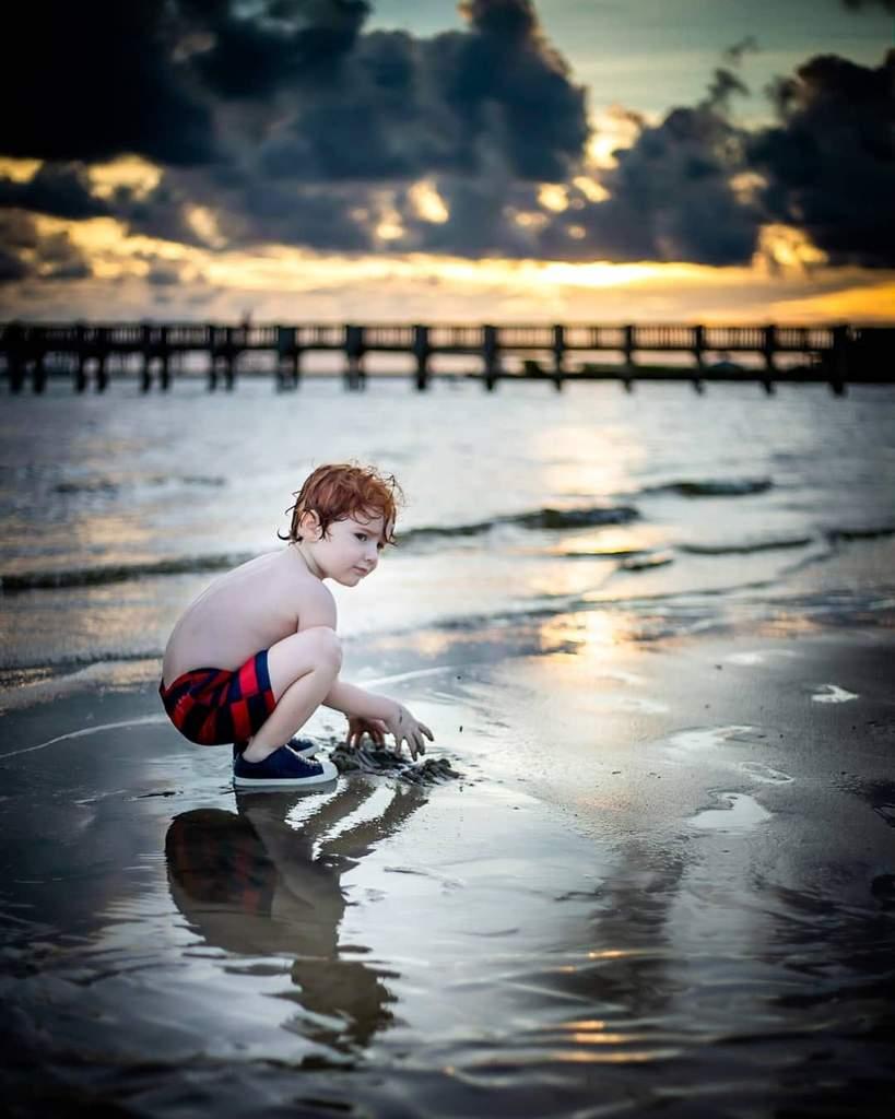 Foto nocturna de un niño jugando en la playa.
