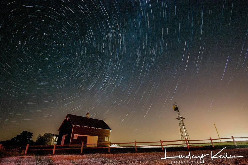 Foto nocturna de cielo estrellado sobre una casa de campo
