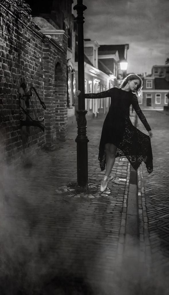 Foto nocturna de mujer sosteniendo un poste de luz