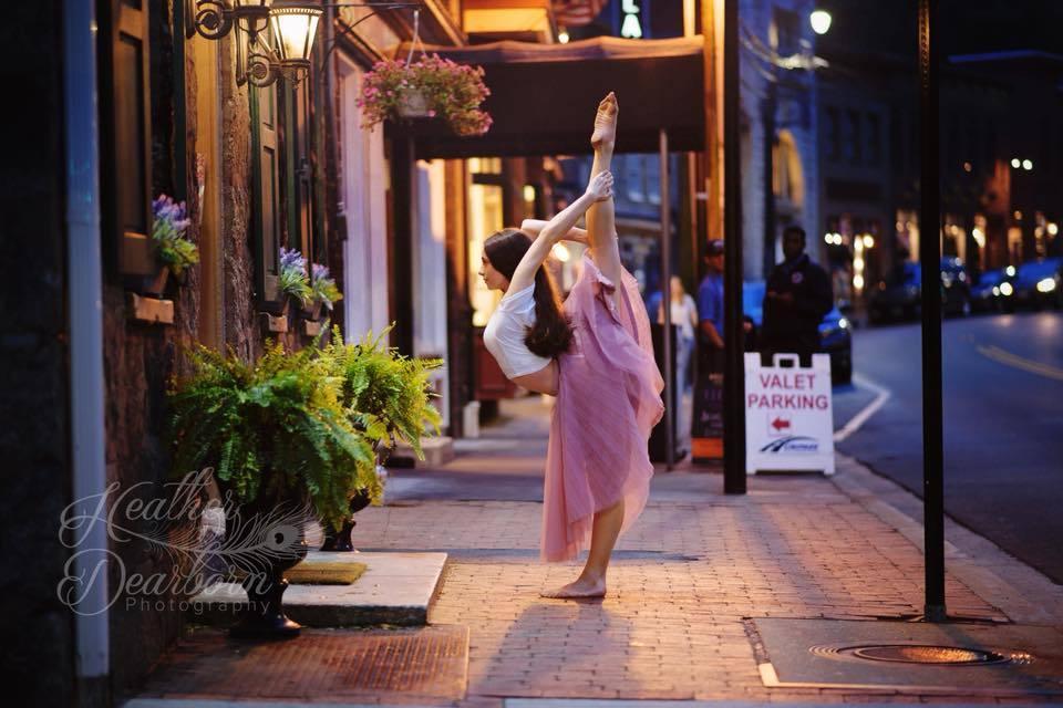 Foto nocturna de bailarina posando en la acera