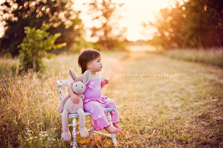 Foto retroiluminada de niña sentada en una silla con su conejito
