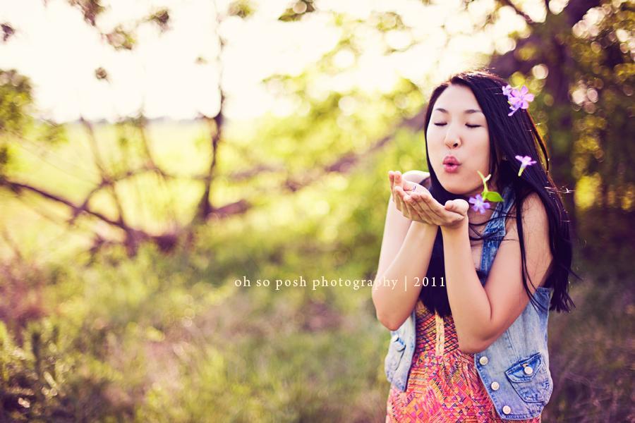 Foto retroiluminada de mujer soplando pétalos de flores de manos