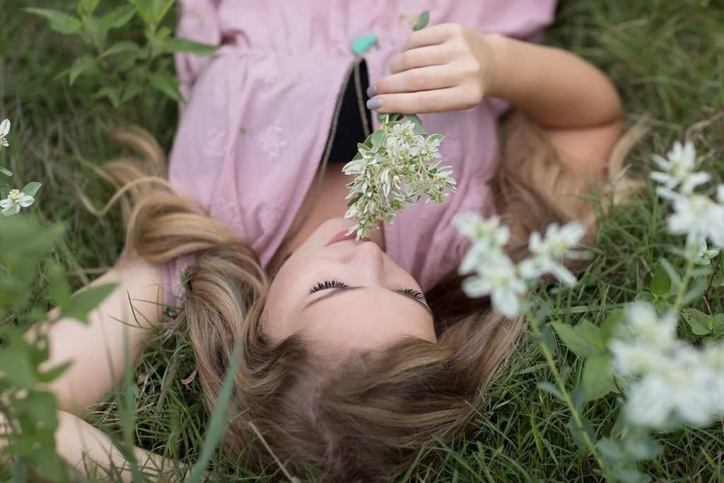 Chica tendida en la hierba con olor a flores oscuro y cambiante editar
