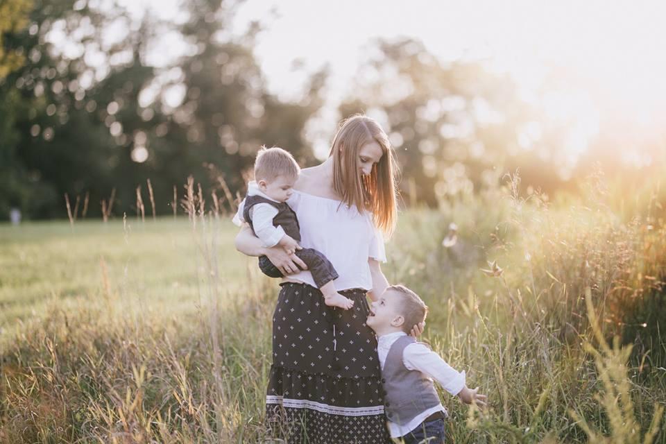 Imagen de familia de madre con dos hijos en un campo al atardecer