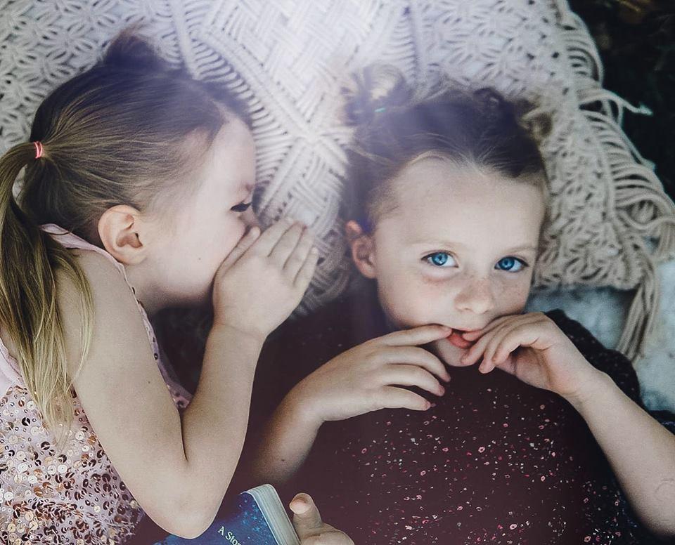 Imagen familiar de hermanas compartiendo secretos