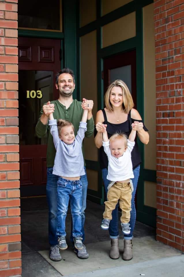 Padre y madre sosteniendo los brazos de los niños para la foto de familia