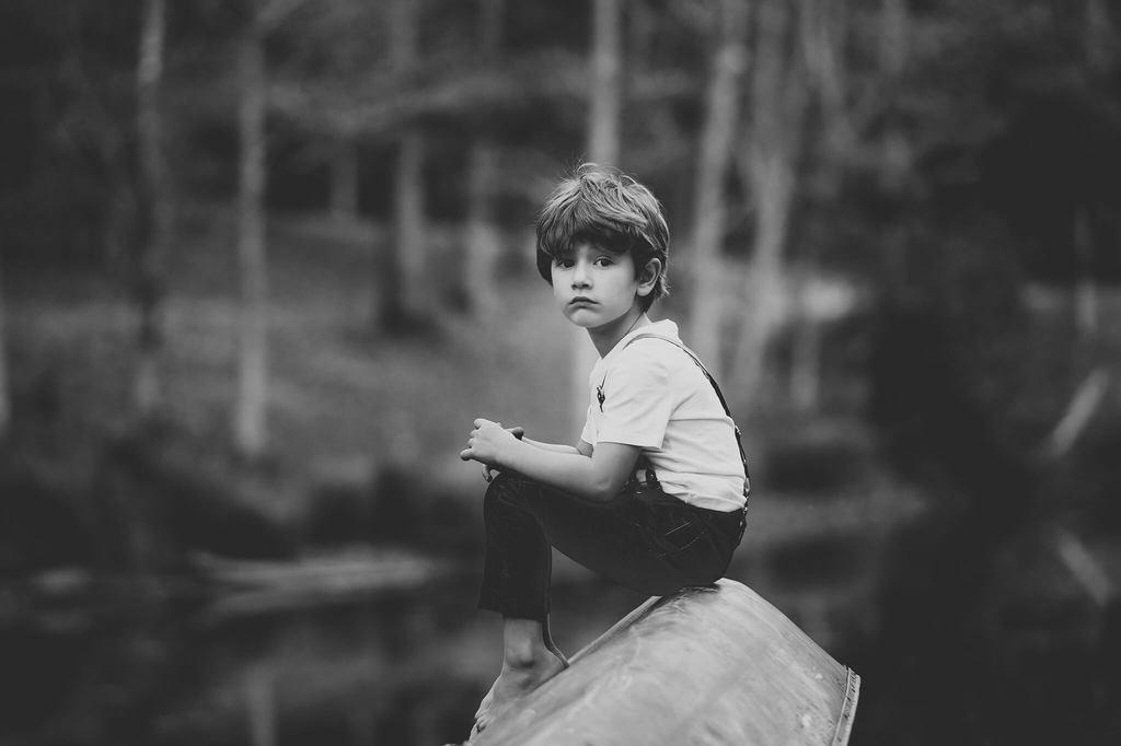 Fotografía en blanco y negro de un niño sentado sobre una roca en un cuerpo de agua