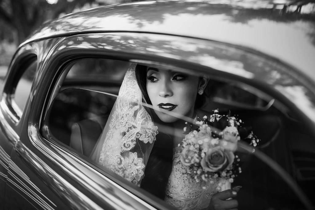 Fotografía en blanco y negro de la novia en coche elegante