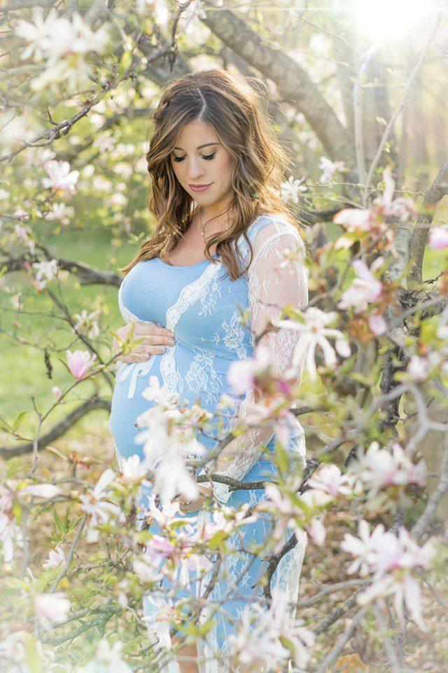 Foto de mujer embarazada posando en flores de primavera