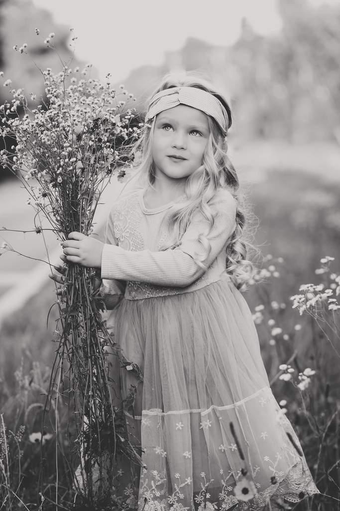 Foto de niña recogiendo flores silvestres de primavera