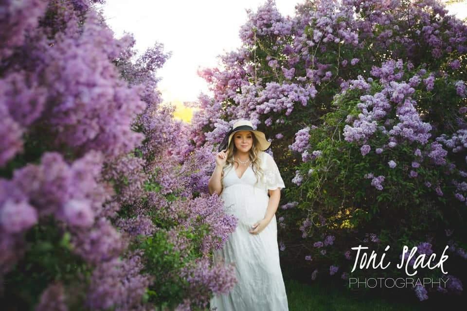 Imagen de maternidad posando en flores de primavera
