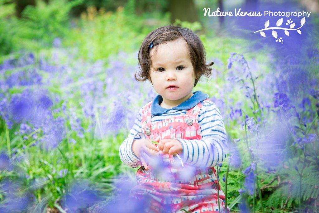 Niño posando en flores de primavera púrpura