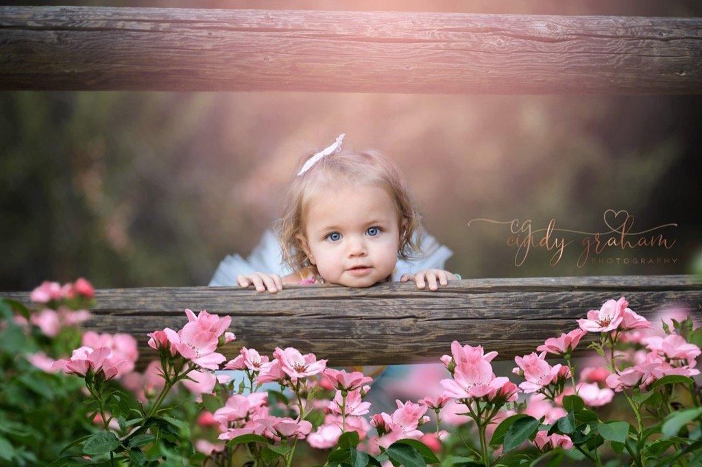 Chica posando detrás de la valla y flores de primavera