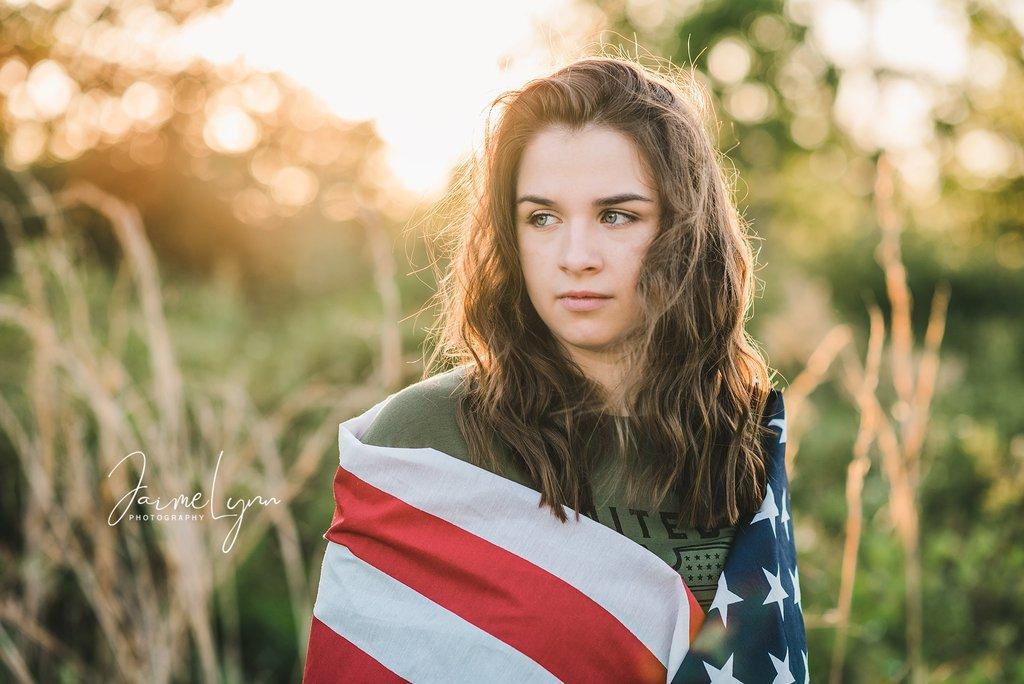 Foto de niña envuelta en bandera estadounidense