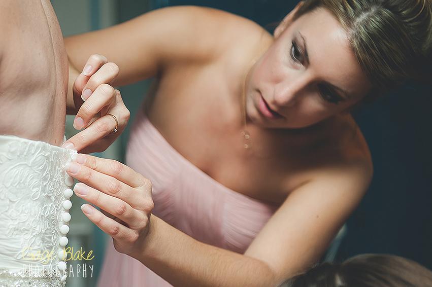 fotografiar bodas - dama de honor ayudando con el vestido