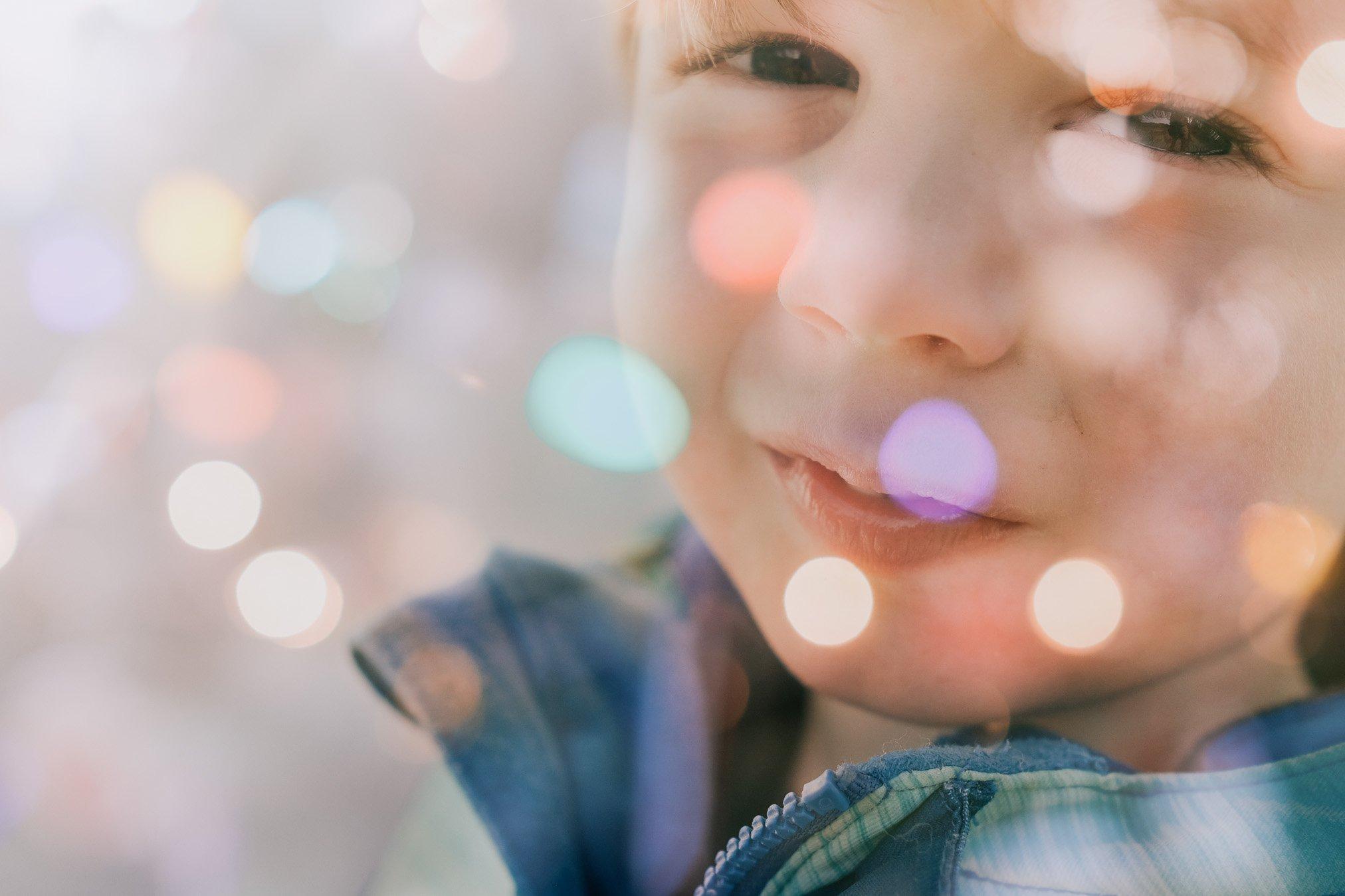 Retrato de niño lindo con luces de bokeh de colores