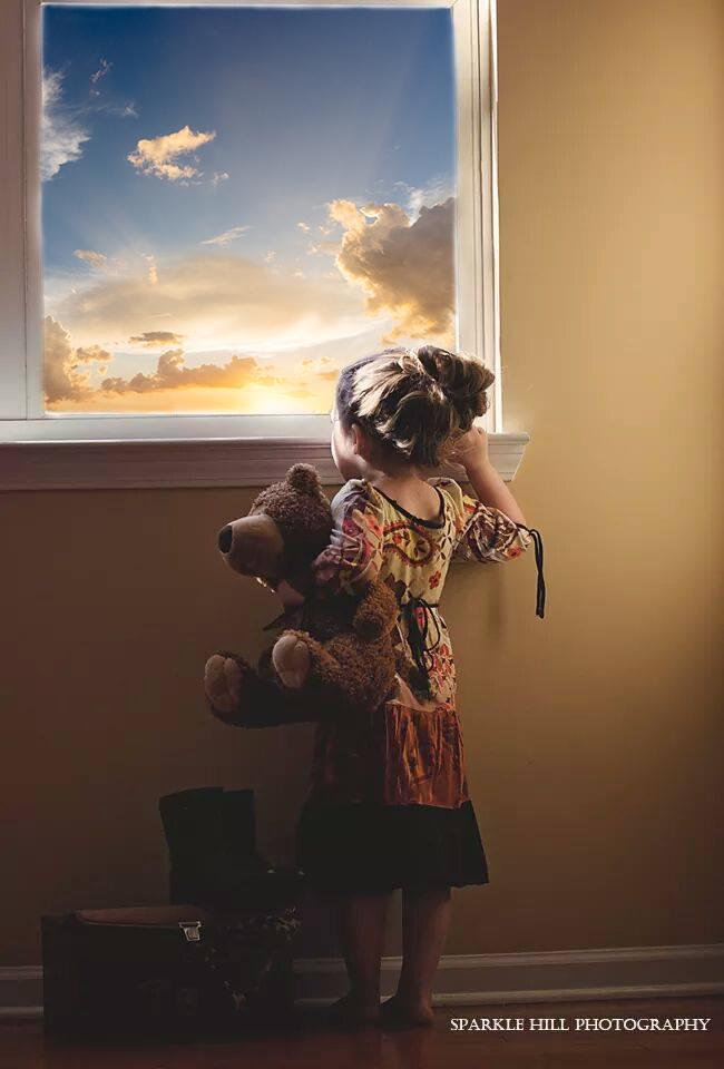 Niña sosteniendo un oso de peluche, mirando por la ventana al hermoso atardecer