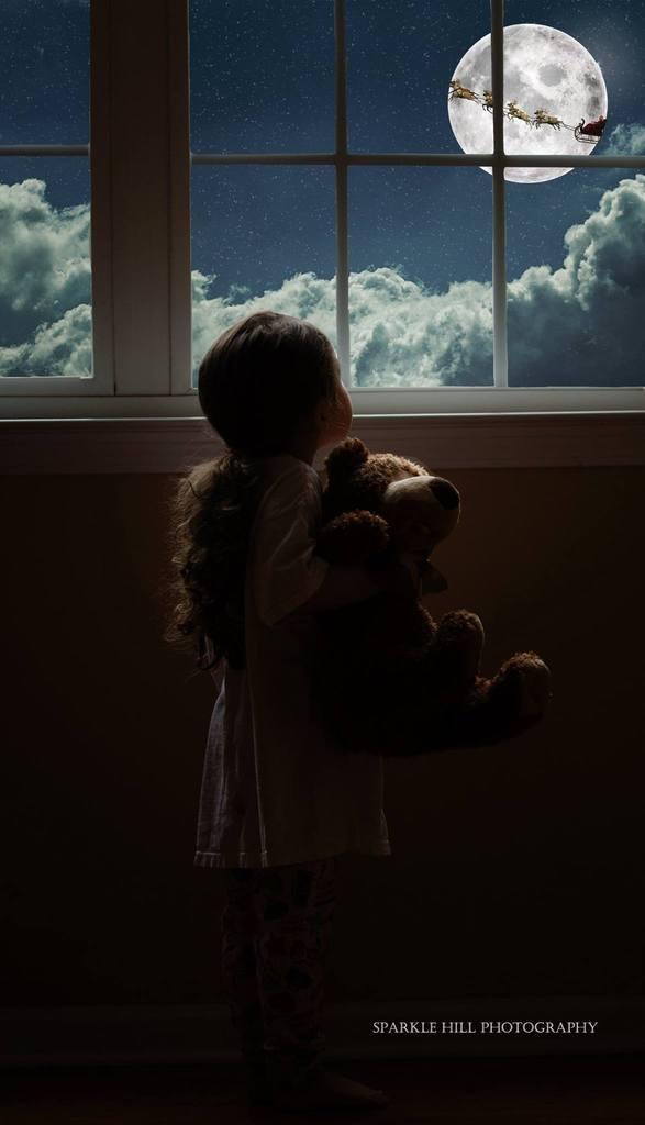 niña mirando por la ventana a la luna, las nubes y el trineo de santa