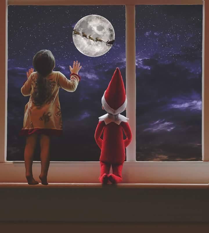 niña y su elfo en el estante mirando por la ventana con superposición de cielo nocturno