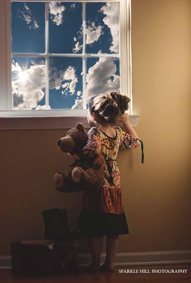 niña con osito de peluche mirando por la ventana con superposición de nubes