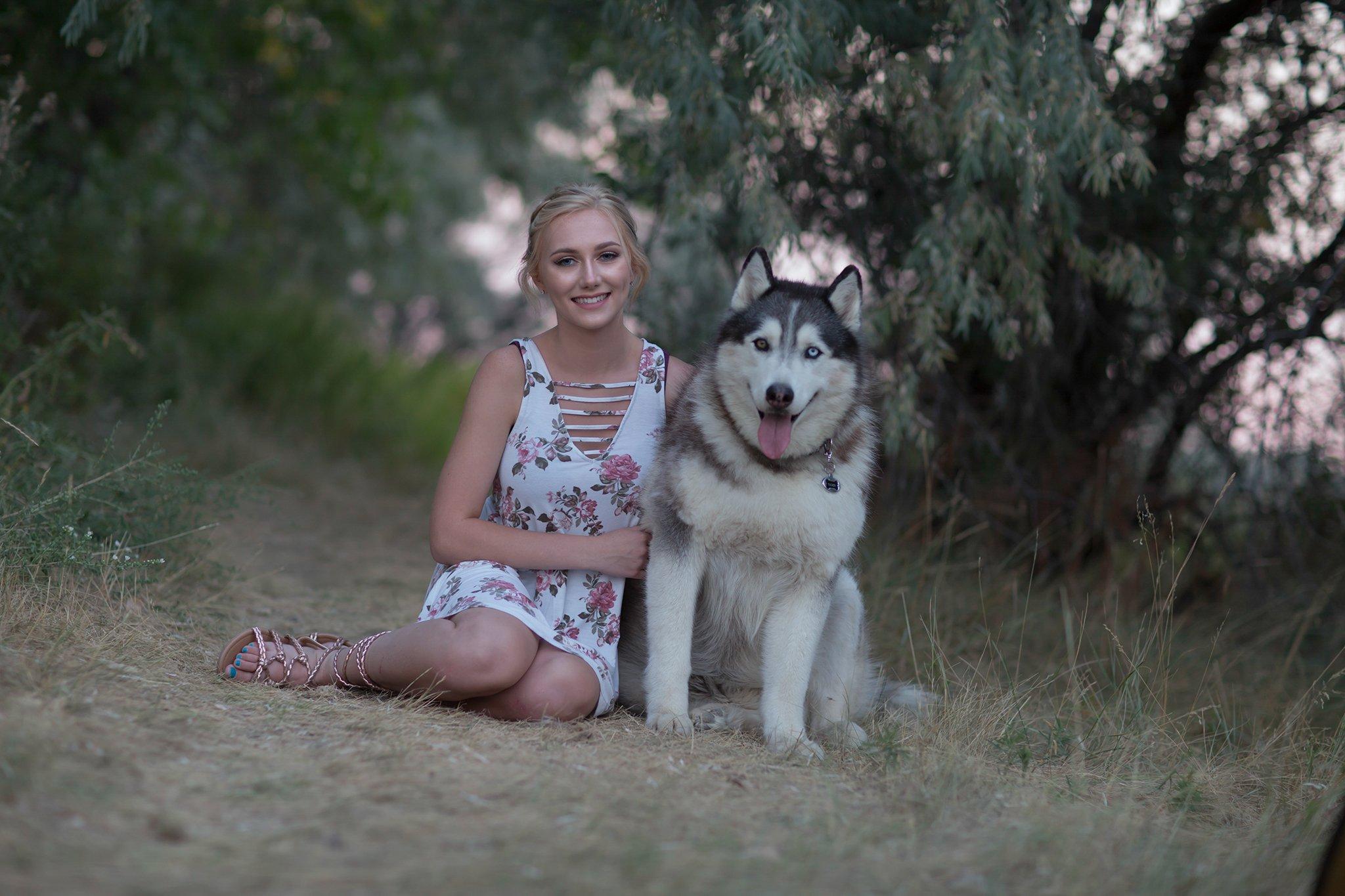 Niña con vestido de flores sentada junto a un perro huskie directamente fuera de la cámara