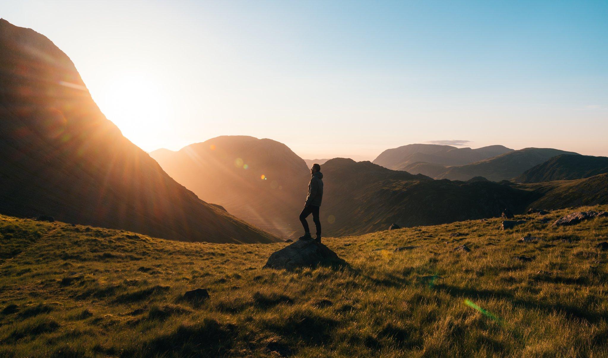 fotografiar la silueta de un hombre en una montaña al amanecer