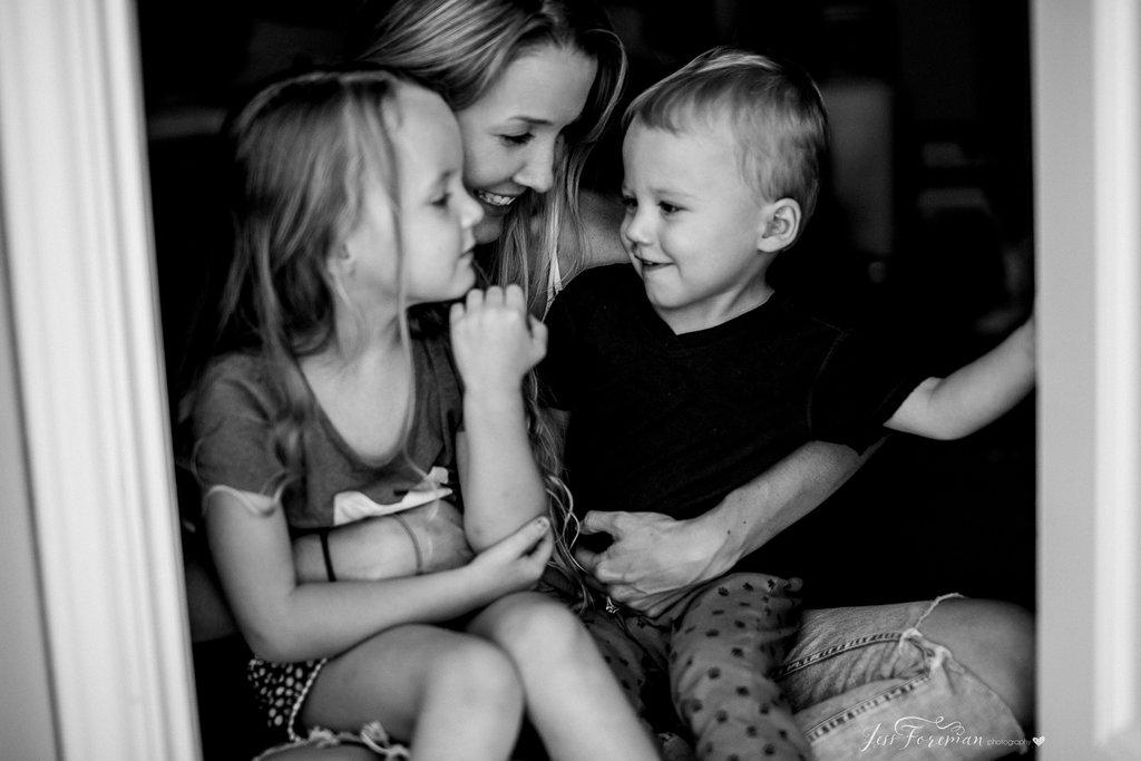 Mamá acurrucada en la foto con sus hijos.