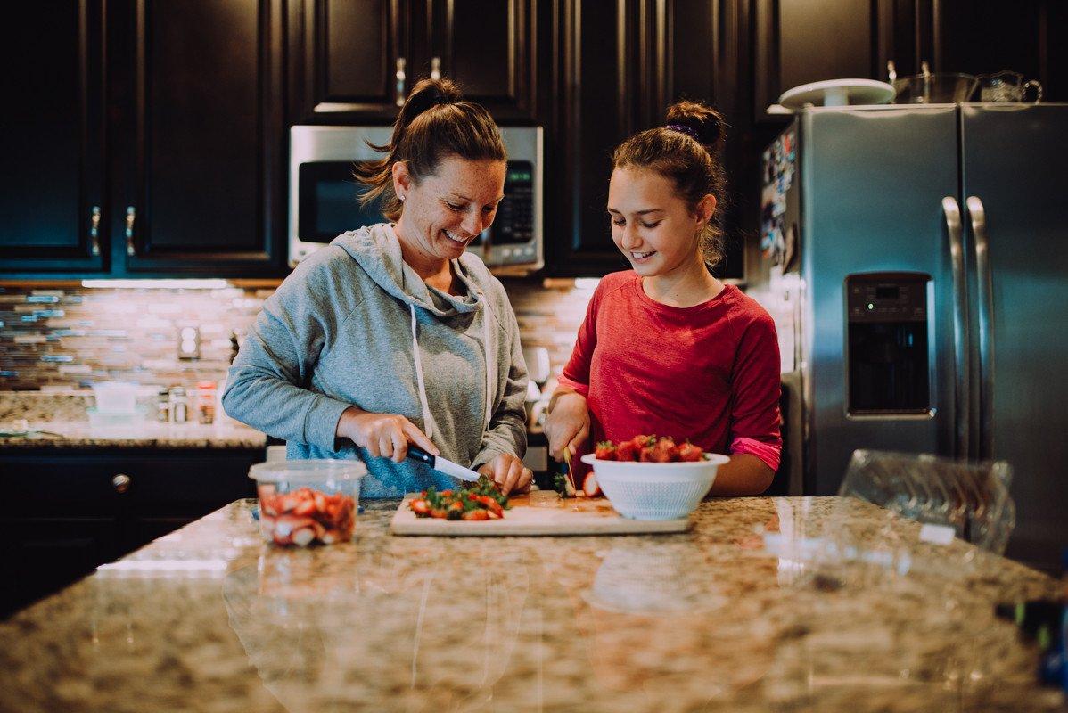 Fotos de una madre y su hija cortando fresas juntas