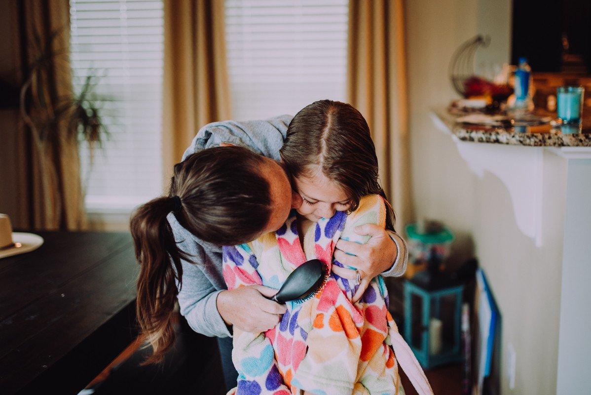 Mamá peinando el cabello de sus hijas con un beso