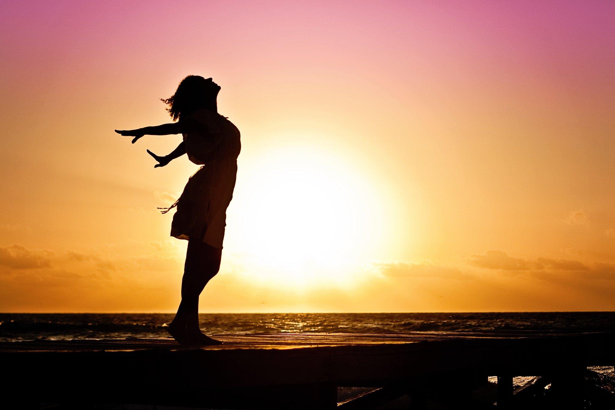 Fotografiar la silueta de una mujer en una playa al atardecer